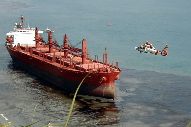 A coastguard's helicopter flies above an